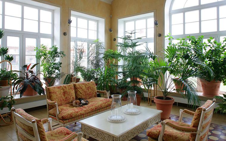 <p>Автор проекта: ДЕКОРА, группа компаний &nbsp;Фотограф: Серебрякова Надежда&nbsp;</p> <p>Просторное помещение наполнено светом и воздухом. Вдоль больших окон с мелкой оранжерейной расстекловкой расставлены зеленые растения, чтобы им досталось побольше света. А в центре комнаты разместилась классическая гостиная, как бы в окружении зимнего сада.&nbsp;</p>