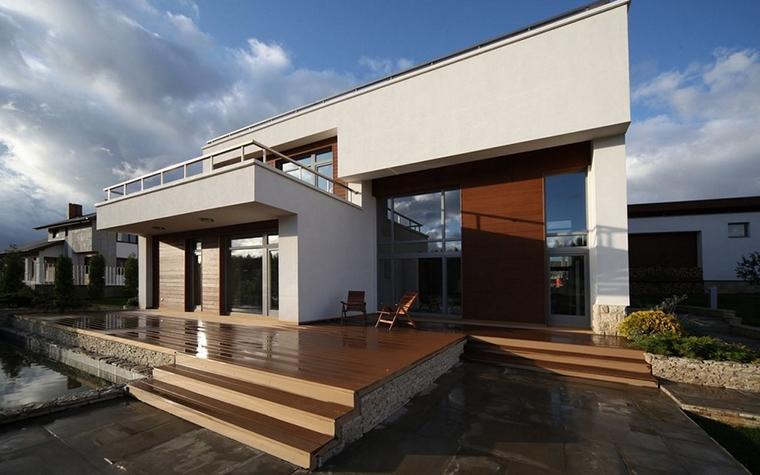 <p>Автор проекта: Гарольд Мосолов &nbsp;</p> <p>Модернистские объемы и линии загородного дома отличает большое количество стекла: окон, дверей, веранд и проч. В них отражается много неба и солнца, как и было задумано. </p>