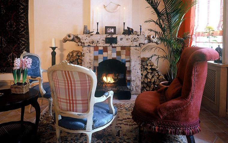 <p>Автор проекта: Юлия Маркос</p> <p>Традиционный дровяной камин стал центром небольшой гостиной, оформленной с элементами этники и классики. По сторонам от необычного каминного портала, украшенного скульптурой и живописью, располагаются стопки дров. Композицию дополняют классические кресла с веселыми обивками под цвет каминной раскраски.</p>