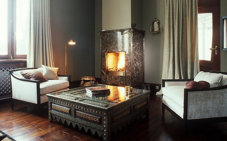 <p>Автор проекта: Анна Муравина</p> <p>В небольшой гостиной была организована уютная каминная зона. Вокруг камина расположились пара кресел в стиле нео ар-деко и низкий этнический стол, украшенный традиционной резьбой по дереву.&nbsp; Камин встроен в выступ стены и имеет красивый фасад, он выполнен из натурального полированного камня с отделкой в стиле модерн.</p>