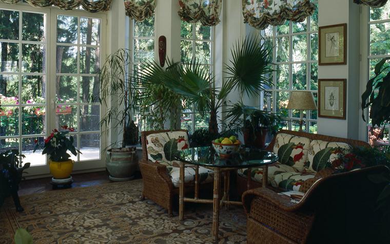 <p>Автор проекта: Анна Муравина</p> <p>Застекленная веранда загородного дома выглядит как тенистая беседка в  саду. Помещение сочетает в себе летнюю гостиную и зимний сад. Интерьер  наполнен живой и декоративной зеленью. Цветущие клумбы и деревья за  окнами, пальмы и фикусы в красивых кашпо, а также отлично подобранный  декор: тропические цветы и листья в мебельных обивках и французских  шторах.&nbsp; </p>