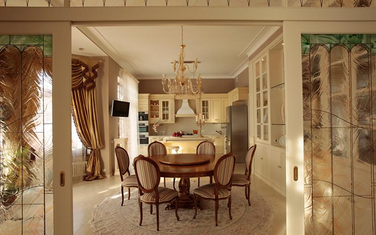 <p>Автор проекта: Style Selva-style&nbsp; Фотограф: Евгений Лучин</p> <p>Классическая гостиная отделяется от просторной кухни-столовой раздвижными перегородками с витражным стеклом. Интерьер наполнен духом итальянской классики. Он и в общей сливочно-золотистой гамме, и в роскошных шелковых драпировках на окнах, и в классической симметричной композиции. Особенно хорош круглый стол, окруженный медальонными стульями, и увенчанный классической хрустальной люстрой с основанием из золотистого металла.</p> <p>&nbsp;</p>