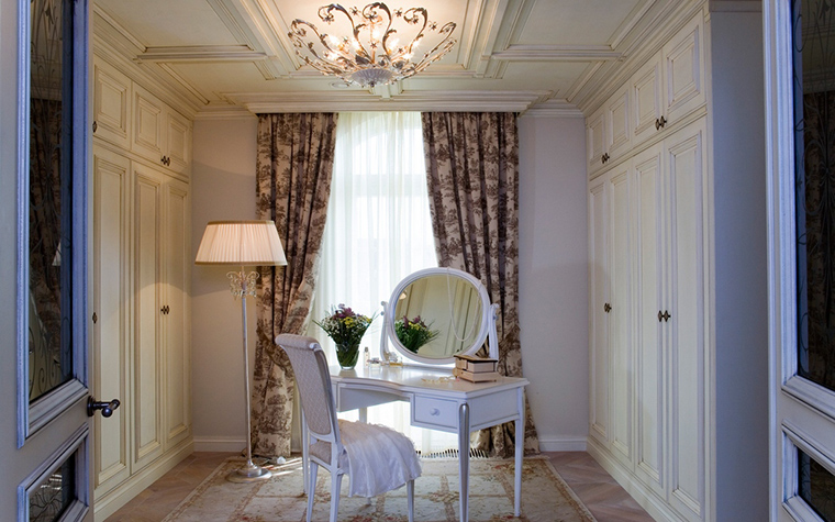 <p>Автор проекта: Доминанта</p> <p>Небольшая гардеробная комната превращена в женский будуар в белых тонах.  Там создана настоящая классическая мизансцена: изящная белая мебель в  окружении белых стен (встроенных шкафов) и на фоне орнаментальной  драпировки. Композицию дополняют витиеватая люстра и стройный торшер.</p>