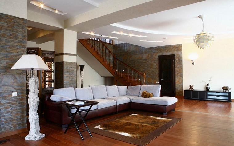 <p>Автор проекта: студия дизайна интерьеров INTERIOR&amp;DECOR.</p> <p>В этом интерьере гостиной стены фрагментарно декорированы камнем. Здесь лестница играет не главную роль. Акценты - на стенах и дизайнерском свете. </p>