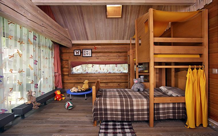 <p>Автор проекта: Март</p> <p>В отделке просторной детской комнаты использованы разнообразные тонировки натурального дерева. Палубная доска пола имеет серо-бежевый тон, по деревянным стенам и мебели явно прошлись морилкой, а потолок с открытыми балками сделали самым светлым, приятного бежево-розоватого тона. </p>