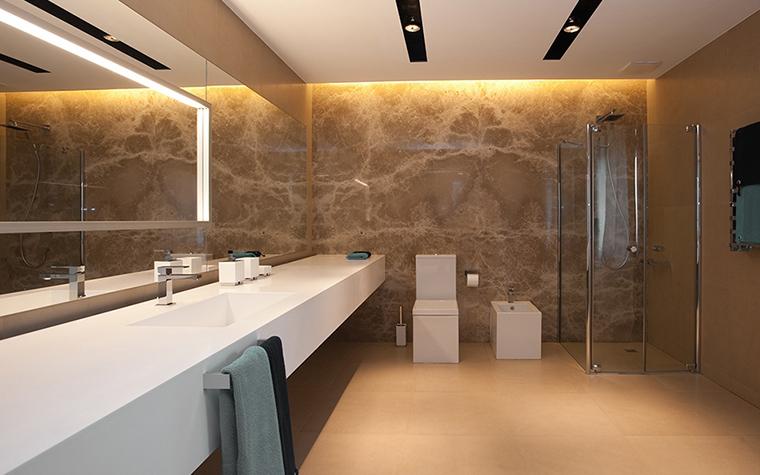 <p>Автор проекта: Юрий Зименко.</p> <p>Минималистичная ванная комната получила стильный световой дизайн. Протяженные горизонтали стен и столешницы подчеркнуты с помощью черных потолочных полос со встроенным светом, а закарнизная подсветка выявляет красивый рисунок стены из натурального камня.</p>