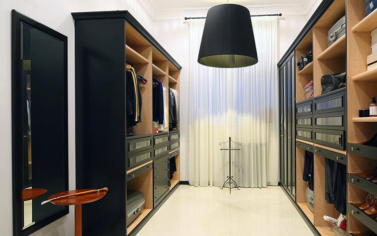 <p>Автор проекта: Domoff Group</p> <p>Гардеробная комната, расположенная в загородном доме, продолжает стиль дорогого ар-деко. Здесь все стильно и элегантно: симметричная композиция черно-коричневой мебели на белом полу, строгое зеркало, изящная напольная вешалка, &nbsp;а также черный плафон на фоне белых драпировок, отмечающий центр симметрии.</p>