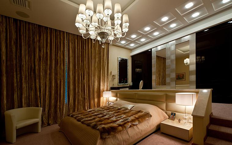 <p>Автор проекта: Егор Серов.</p> <p>Спальня оформлена в стиле современной классики с пышными драпировками и роскошным парадным светом. Прямо над кроватью размещена большая многорожковая люстра, а будуарная зона с туалетным столиком и зеркалами освещается двумя рядами встроенных точечных ламп.</p>