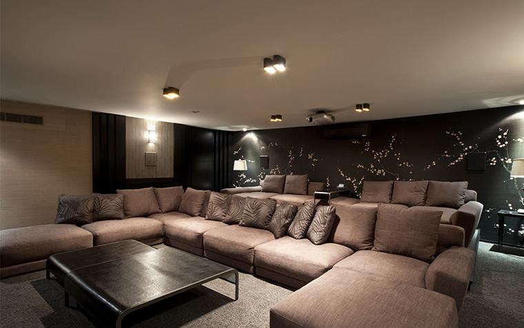 <p>Автор проекта: Егор Серов</p> <p>Серия горизонтальных и угловых диванов, организованных в два ряда, создали удобный зрительный зал для гостиной с домашним кинотеатром.</p>