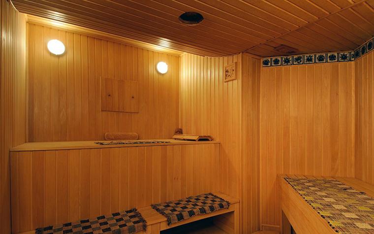 <p>Автор проекта: Егор Серов</p> <p>Помещение бани в загородном доме имеет необычную конфигурацию. По традиции все поверхности обшиты деревом и устроено множество полок-лежанок на разных уровнях. Небольшой орнаментальный фриз из керамической плитки и подстилки с шахматным рисунком стали украшением деревянного интерьера.&nbsp; </p>