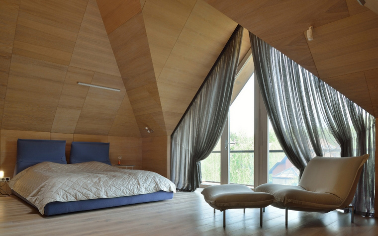 <p>Автор проекта: АИ-Студия<br /> Фотограф: Алексей Народицкий</p> <p>Главное украшение этой мансардной спальни - сложная архитектура стен и потолка, деревянные облицовки, а также громадное французское окно треугольной формы.&nbsp; А обстановка была создана самая минимальная: низкая кровать, красивые оконные драпировки и кресло с пуфом от знаменитого Паскаля Мурга.</p>