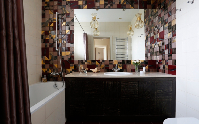 <p>Автор проекта: А-Дизайн</p> <p>Главным украшением небольшой совмещенной ванной комнаты стала отделка стены, вдоль которой расположена раковина, вмонтированная в комод. Орнаментальный декор, собранный из кусочков разноцветной плитки, эффектно преобразил все помещение.</p>