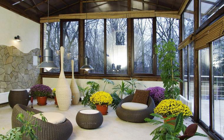 <p>Автор проекта: Погорельчук Владимир</p> <p>Застекленная веранда загородного дома оформлена стильно и модно. Там создана симпатичная композиция из живых цветов и растений в кашпо, рядом с которыми расставлена легкая плетеная мебель и дизайнерская скульптура органических форм. Летом, вся мебельная обстановка вместе с растениями легко перемещается на открытую террасу.&nbsp;</p>