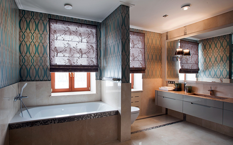 <p>Автор проекта:   Mill-Studio</p> <p>Просторная ванная комната в загородном доме имеет удобную планировку и красивый декор. В обицовке стен сочетаются полированная керамическая плитка, под мрамор, а верхняя часть стен украшена орнаментальной мозаикой. С мозаичными узорами отлично сочетаются текстильные ролы на окнах с изящным раппортным рисунком в духе рококо.</p>