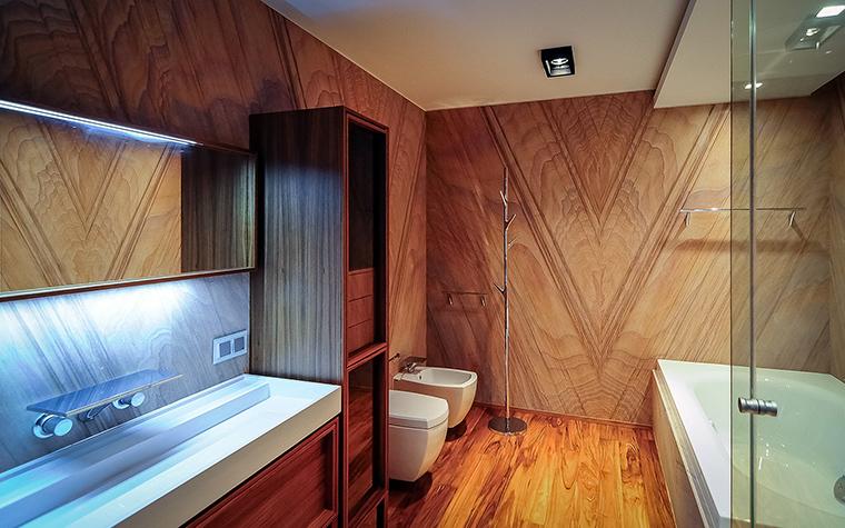 <p>Автор проекта:   Volume-X</p> <p>Зеркало в ванной комнате подсвечено с помощью узкого длинного светильника. Поскольку светильник расположен сверху от зеркала, он заодно освещает и столешницу с длинной раковиной. Подсветка имеет холодный светло-голубой цвет, что интересно контрастирует с теплой гаммой натуральных облицовок. </p>