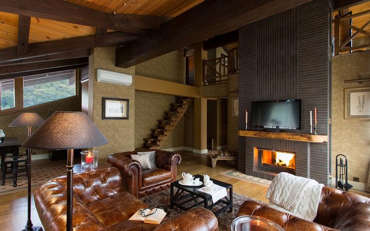 <p>Автор проекта: Юрий Зубенко</p> <p>В этой двухуровневой гостиной есть английский дух. Потолочные балки выкрашены в темный цвет, диваны из темной стеганой кожи, орнаментальные ковры и, конечно, пылающий камин. </p>