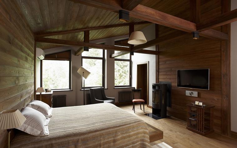 <p>Автор проекта: Алексей Розенберг</p> <p>Спальня в подмосковном загородном доме выглядит очень по-европейски. Открытые конструкции потолка, панорамные окна, темные тонировки деревянных стен и пола, отсутствие декора - все это выдает почерк архитектора-модерниста.</p>