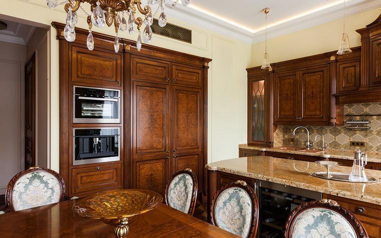 <p>Автор проекта:   Архитектурное бюро ПЛАН</p> <p>Классические кухонные шкафы из красного дерева, мраморные столешницы, медальонные стулья с узорными обивками роднят обстановку кухни с английской классикой.</p>