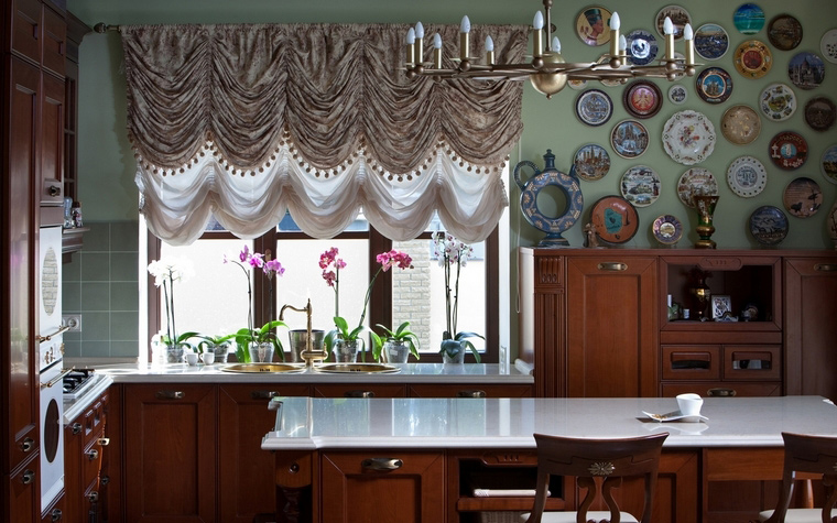 <p>Автор проекта: SBM studio Фотограф: Андрей Авдеенко</p> <p>Просторная кухня выдержана в стиле английской классики с фигурной мебелью цвета красного дерева, пышными французскими шторами и цветными стенами. Оливково-зеленые стены стали отличным фоном для композиции из декоративных тарелок. А красивые оконные переплеты стали рамой для коллекции изящных орхидей.</p>