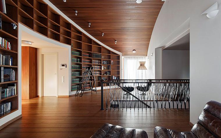 <p>Автор проекта:   KV-BURO</p> <p>С помощью оригинального авторского стеллажа оформлена целая стена просторного холла, расположенного на втором этаже загородного дома. </p>