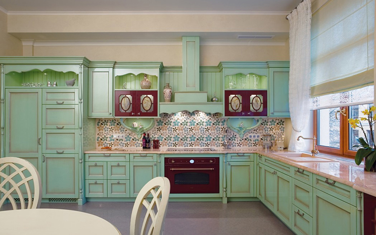 <p>Автор проекта: Наталья Дышлова</p> <p>Кухня в стиле прованс была оборудована большим кухонным гарнитуром, выполненном в едином светло-бирюзовом цвете. Ярким дополнением к нежной бирюзе стали красно-коричневые вставки фасадов и дверь духового шкафа, а также традиционная для прованса столовая деревянная мебель, выкрашенная в белый цвет.&nbsp;</p>