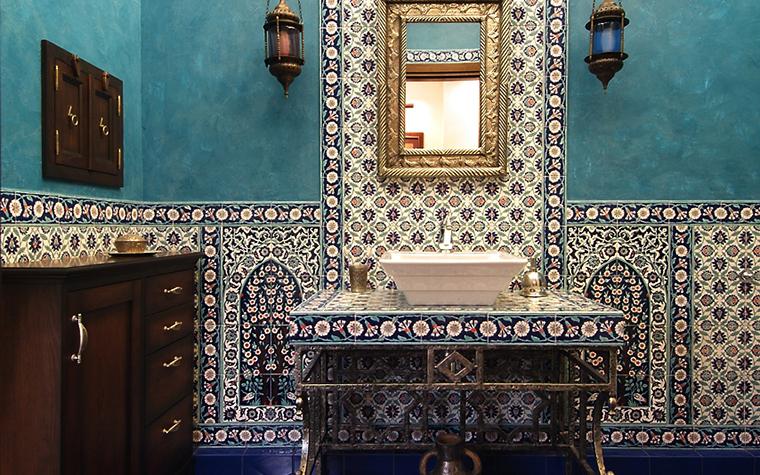 <p>Автор проекта: К-СТУДИЯ</p> <p>Ванная комната оформлена в цветах и орнаментах традиционного марокканского дома. Верхняя часть стен выкрашена в цвет морской волны, а по низу пущена широкая полоса, выложенная из орнаментальной плитки. На фоне ярких бирюзовых стен эффектно смотрятся лампы-фонари из цветного стекла, а фоном для зеркала стало не менее эффектное панно, выложенное&nbsp; из той же узорной керамической плитки.&nbsp; </p>