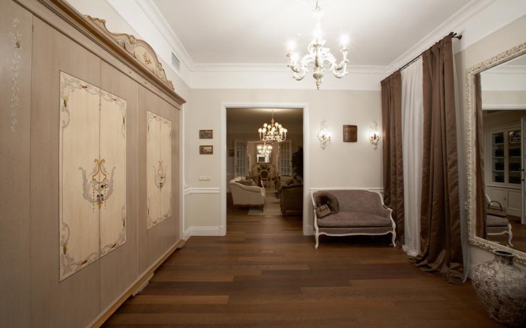 <p>Автор проекта: Кисель Марина</p> <p>Просторная гардеробная соединена с гостиной и выдержана в едином классическом стиле и бежево-коричневом монохроме. Комната соединила в себе несколько функций: закрытую систему хранения и камерную гостиную с изящным диваном, зеркалами и хрустальными светильниками и люстрой. </p>