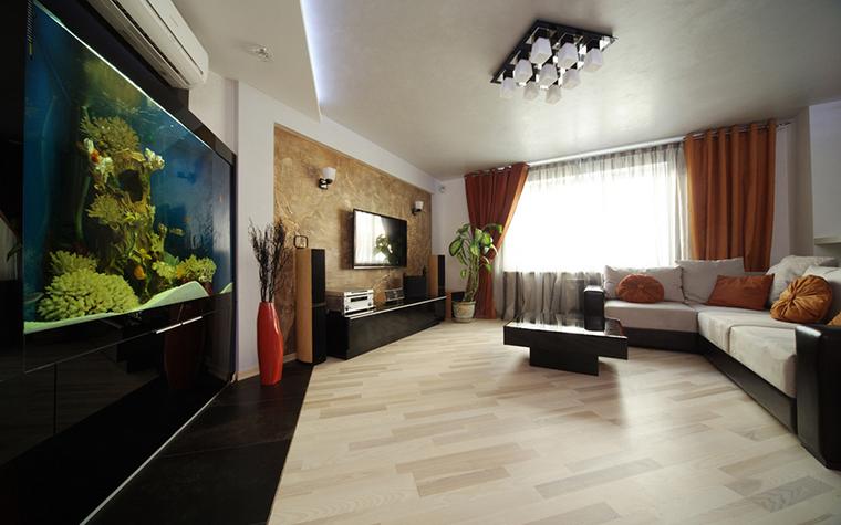 <p>Автор проекта: студия дизайна ARTpeople.&nbsp;</p> <p>Алая керамическая ваза неправильной фрмы хорошо рифмуется в многоугольной гостиной не только с аквариумом и комнатными растениями, но и с диванами, текстилем.</p>