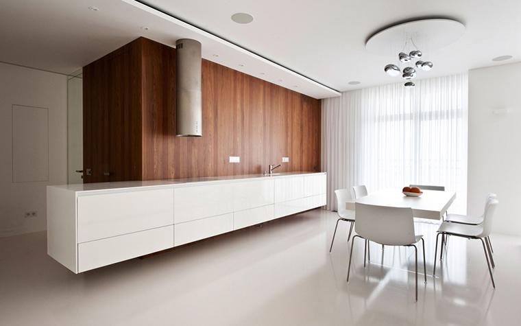 <p>Автор проекта: Александра Фёдорова. Фотограф: Александр Камачкин.</p> <p>Фрагмент стены, облицованный деревянными панелями, придает четкие очертания монохромной кухне.</p>