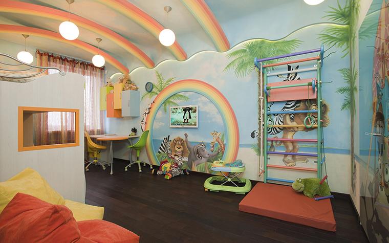 <p>Автор проекта: Наталья Фарносова</p> <p>Детская комната оформлена в ярких оптимистичных цветах и с игровым декором и дизайном. Здесь есть двухуровневая кровать, шведская стенка, яркие кресла-мешки, но главная декоративная находка этого интерьера - цветные радуги. Они украшают потолок и стены. Кроме разноцветных радуг стены разрисованы яркими картинками из детских мультфильмов.</p>