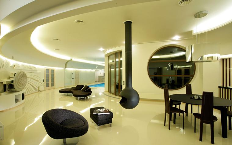 <p>Автор проекта: Архитектурная мастерская Studio68/32&nbsp;</p> <p>В абсолютно белом интерьере закругленной гостиной все поверхности имеют глянцевые финиши. На этом блестящем белом фоне отлично смотрится черная графичная мебель, а также&nbsp; спускающийся с потолка подвесной камин, напоминающий светильник.</p>