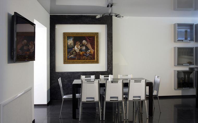 <p>Картина в золоченой раме стала главным украшением минималистичной столовой. Чтобы подтвердить значимость живописного полотна его поместили внутрь деревянной панели, которая&nbsp; создает эффект двойной рамы. </p>