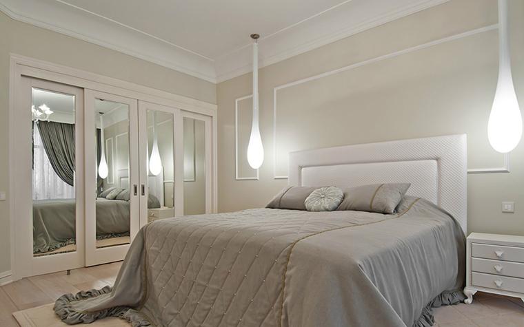 <p>Автор проекта: Андрей Ексарев</p> <p>Спальня в модных серо-белых тонах очень эффектно освещена. Большую кровать с высоким прямоугольным изголовьем, как стражи фланкируют две потолочные лампы - светящихся капли, свет которых умножается в многочисленных зеркалах. </p>