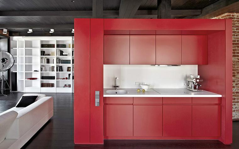 <p>Автор проекта: студия Studioplan.</p> <p>Яркая красная корпусная кухонная мебель выполняет роль цветового акцента и помогает визуально выделить кухню в open-space.</p>