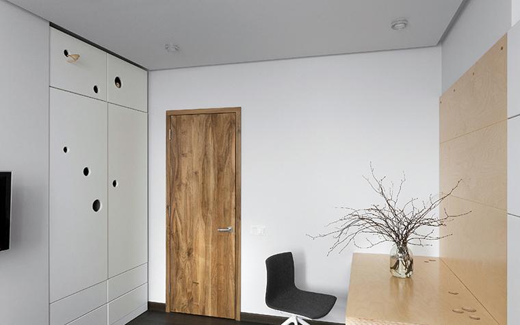 <p>Автор проекта: Ryntovt Design</p> <p>Белоснежный интерьер детской комнаты очень оживили деревянные детали: дверь из текстурного дерева и настенное панно, переходящее в рабочую столешницу.</p>