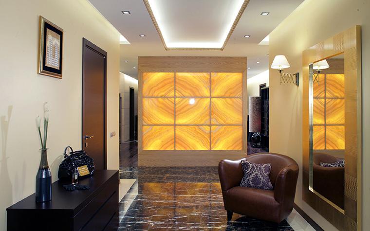 <p>Автор проекта: Армен Мелконян.&nbsp;</p> <p>Навесной потолок гостиной оснащен сложной многоуровневой светосистемой. Центр потолка выделен с помощью светодиодной подсветки, по бокам которого расположены точечные светильники.</p>