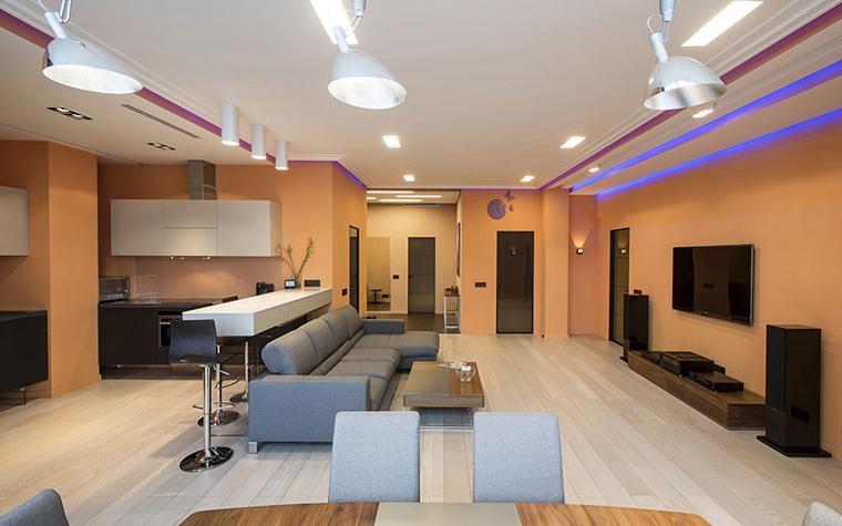 <p>Автор проекта: архитектурная студия Sky Gallery. Фотограф: Александр Камачкин.</p> <p>Приглушенный оранжевый цвет стен является объединяющим фоном. Разделяют же зоны традиционно диван и барная стойка для завтраков. </p>