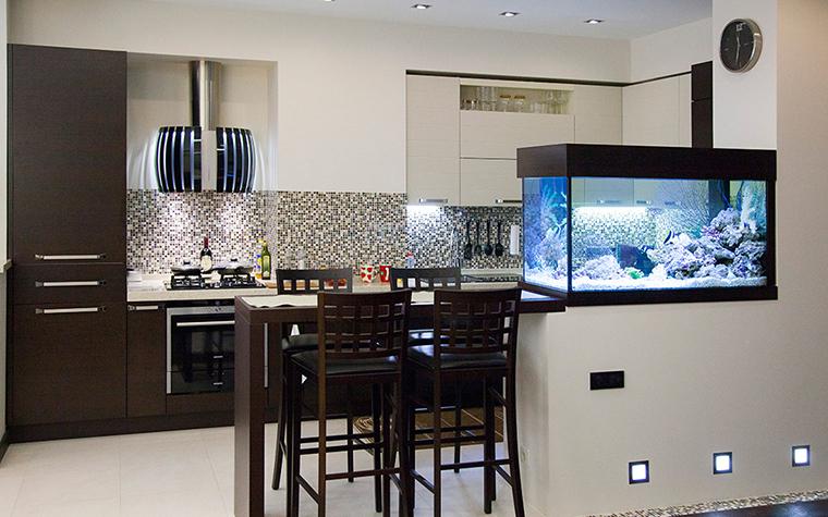 <p>Автор проекта: Анна Савикова.&nbsp;</p> <p>Открытая кухня, соединенная с гостиной большим аквариумом,&nbsp; получила мозаичную отделку с намеком на аква&nbsp;тему.&nbsp; Широкая полоса над рабочей поверхностью кухни облицована разноцветной мозаикой, которая издалека напоминает мелкую&nbsp; морскую гальку. </p>