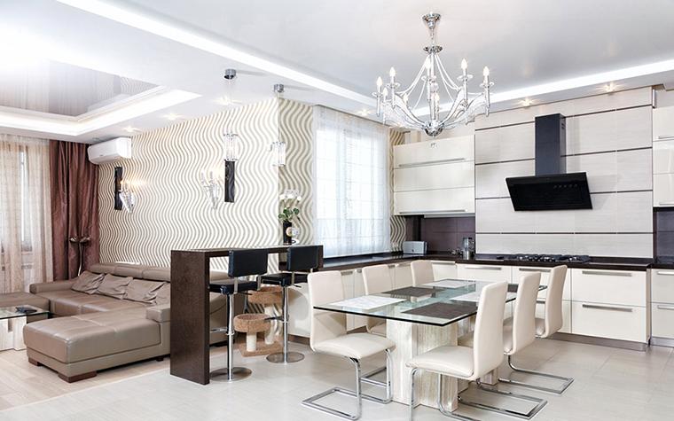<p>Автор проекта: Вера Белова.</p> <p>Этот белый опенспейс гостиной -кухни условно разделен барной стойкой с высокими стульями.</p>