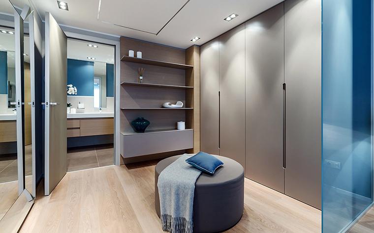 <p>Автор проекта:   NG-Studio</p> <p>Гардеробная комната&nbsp; расположена по соседству со спальней и санузлом.  Помещение выдержано в современном стиле и оборудовано закрывающимися  шкафами, один из которых зеркальный. В центре помещения солирует круглый  пуф для примерок.</p>