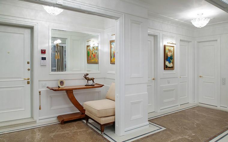 <p>Автор проекта: Елена Битулeва</p> <p>Все стены просторной прихожей отделаны белыми панелями с классическими филенками. В них отлично вписались зеркала и цветные картины.&nbsp;</p>