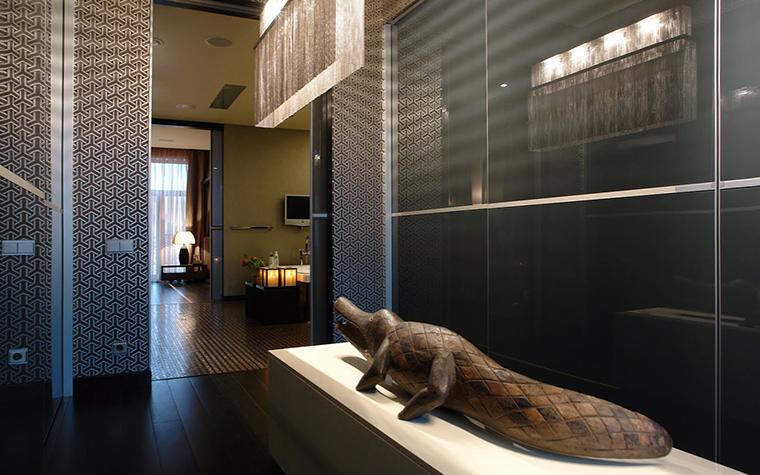 <p>Автор проекта: Марина Гисич</p> <p>Гардеробная комната оформлена в стиле современного ар-деко. Помещение больше напоминает холл с модной скульптурой, чем гардеробную. Вся система хранения скрыта за панелями из матового стекла, стены украшают орнаментальные обои, на постаменте - деревянный крокодил, подсвеченный ар-декошной люстрой. Очень стильно! </p>