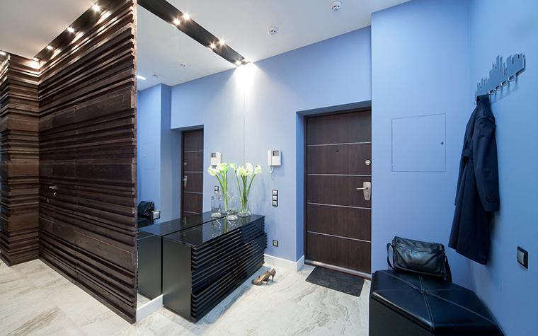 <p>Автор проекта: Алеся Сахно</p> <p>В декоре прихожей соединились серо-белый мрамор пола, голубая покраска стен входной зоны и настенные панели из темного дерева панели, которые выглядят как рельефные панно.&nbsp;</p>