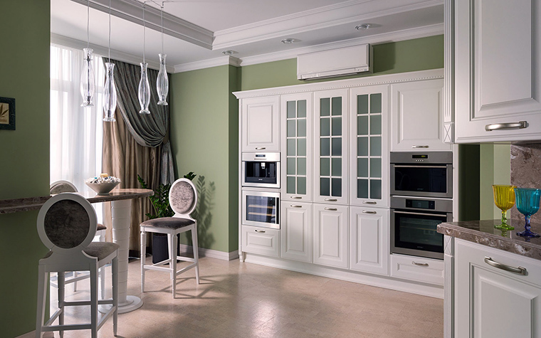 <p>Автор проекта: Алеся Сахно</p> <p>Открытая кухня в проекте Алеси Сахно оформлена в стиле современной классики. Дизайнер нашла нестандартное решение и поместила белую встроенную кухню на фоне зелено-оливковых стен. К белоснежным филенчатым фасадам отлично подобраны белые барные стулья и стильные лампы из прозрачного стекла.</p>