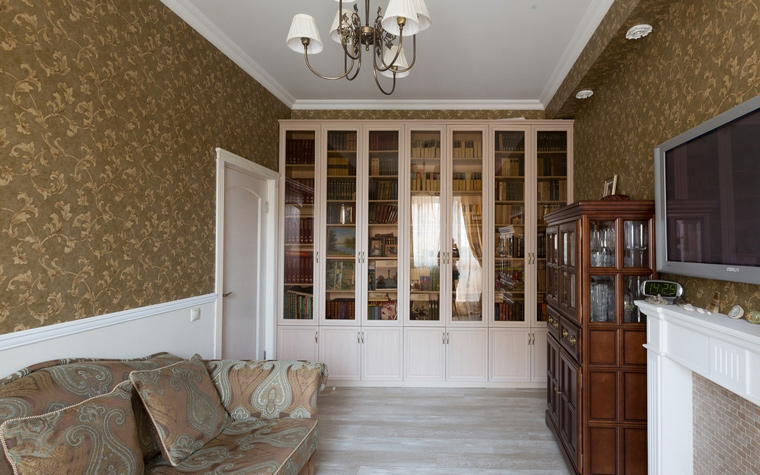 <p>Автор проекта: Марина Саркисян</p> <p>Одна из стен гостиной оборудована высокими застекленными шкафами, там хранится вся домашняя библиотека. </p>