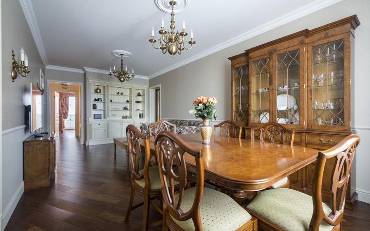 <p>Автор проекта: Екатерина Сережина</p> <p>Просторная гостиная, оформленная в стиле английской классики, оборудована двумя большими посудными шкафами, где наряду с функциональной посудой выставлены и декоративные тарелки и блюда. Один из шкафов входит в коллекцию столовой мебели, выполненной в натуральном дереве, а другой - сделан на заказ и покрашен в тон стен.</p>