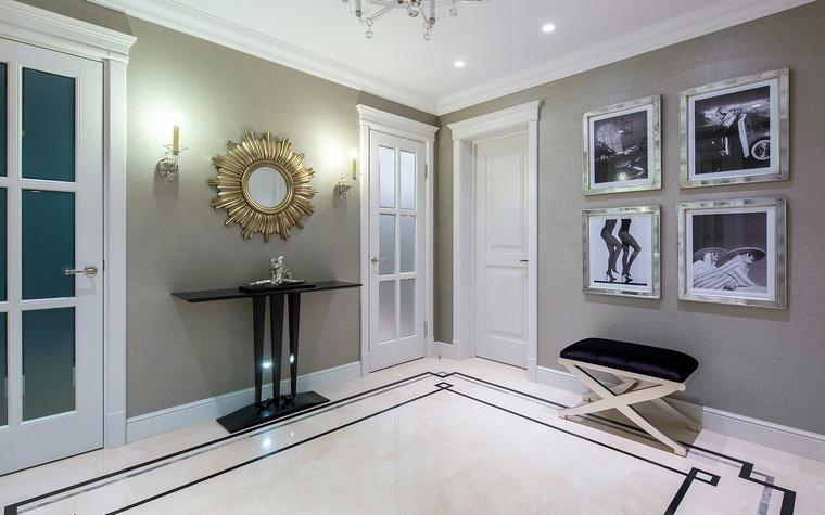 <p>Автор проекта: Полина Пидцан</p> <p>Холл оформлен в стиле современной классики с элементами ар-деко. Интерьер безупречно декорирован: мягкий монохром, черная графичная мебель, красивый рисунок пола. А стены украшены модными фэшн фото и зеркалом в золоченой раме.&nbsp;</p>