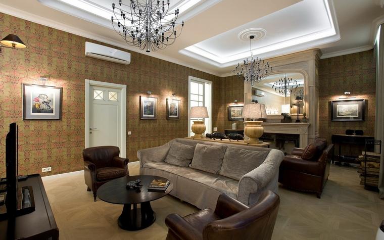 <p>Автор проекта: Юрий Зубенко</p> <p>В просторной гостиной, оформленной в классическом духе, применена потолочная закарнизная подсветка. Потолочные ниши с подсветкой не только украшают интерьер, но и выполняют функцию зонирования пространства гостиной. Графика, развешенная по стенам, оснащена специальными светильниками, которые подсвечивают каждый лист индивидуально.</p>