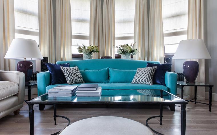 <p>Автор проекта: I.D. Interior Design</p> <p>Бирюзовый диван, окруженный парными лампами, выставлен в полукруглом эркере как на театральной сцене.&nbsp;</p>