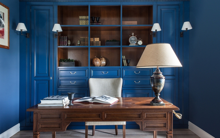 <p>Автор проекта: I.D. Interior Design</p> <p>Красивый модульный стеллаж ярко синего цвета оформил стену кабинета за рабочим столом.&nbsp; Стеллаж не только красив, но и очень удобен. Он включает в себя открытые полки, закрытые вертикальные шкафы и множество ящиков. Чтобы поддержать эффектный цвет, авторы проекта продолжили его и на стенах. </p>